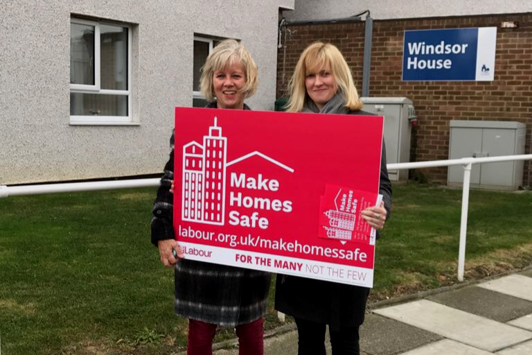 "Bernadette and Rosie holsing ""Make Homes Safe"" sign outside Windsor House"